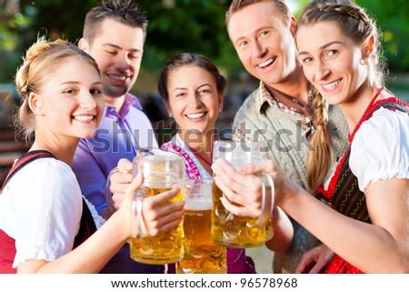 In Beer garden - friends in Lederhosen drinking a fresh beer in Bavaria, Germany - stock photo