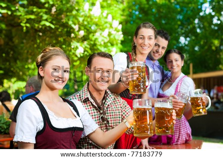 In Beer garden - friends in Tracht, Dindl and Lederhosen drinking a fresh beer in Bavaria, Germany - stock photo