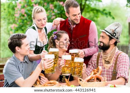 In Beer garden - friends in Tracht, Dirndl and Lederhosen drinking a fresh beer in Bavaria, Munich, Germany - stock photo