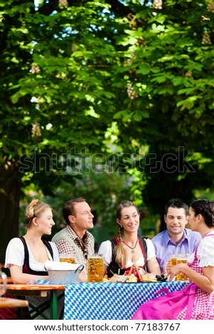 In Beer garden - friends Tracht, Dindl and on a table with beer and snacks in Bavaria, Germany - stock photo