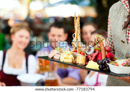In Beer garden in Bavaria, Germany - beer and snacks are served; focus on meal - stock photo