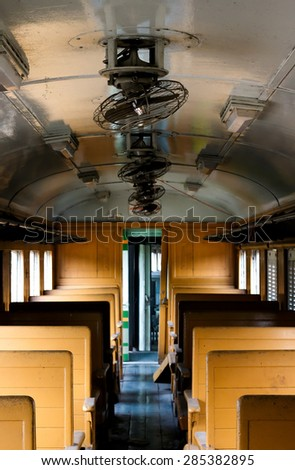 In bogie of old railway wagon. Inside are wooden bench seats and old electrical fan. - stock photo