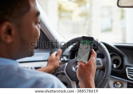 In car view of young male African American looking at maps app on his phone - stock photo