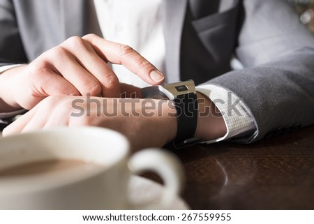 In coffee bar a man using his smartwatch. Close-up hands - stock photo