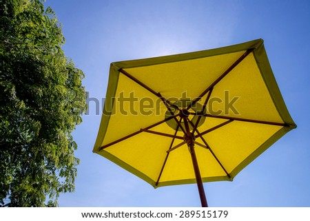 In daylight summer time under the sun leaving the strong sunlight by Yellow Sunshade that stand near by the tree over blue sky - stock photo