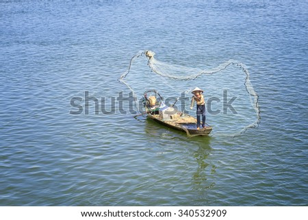 In Dong Nai, Vietnam - November 15th, 2015: The fishermen casting their nets to catch the fish survive better improve the lives winter morning at Tri An, Dong Nai, Vietnam