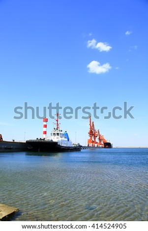 In freight terminal, gantry crane and cargo ships are in loading and unloading of goods