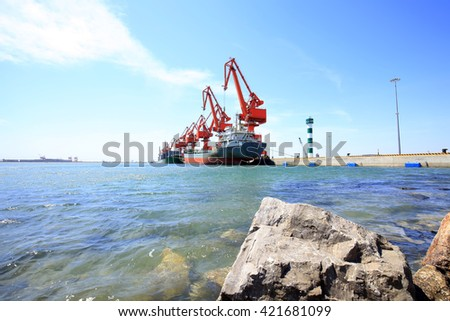 In freight terminal, gantry crane and cargo ships are in loading and unloading of goods - stock photo