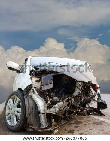 In front of a white car was demolished in an accident with a cloudy sky background. - stock photo