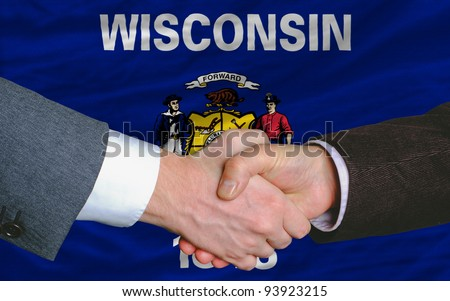 in front of american state flag of wisconsin two businessmen handshake after good deal - stock photo