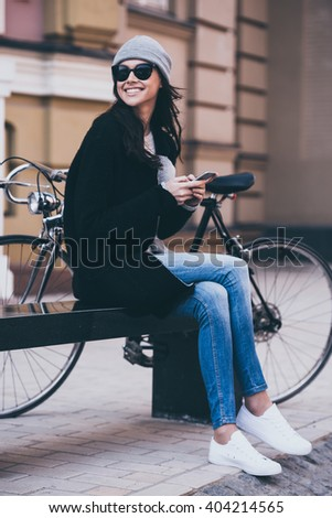 In great mood today.  Side view of beautiful young woman in sunglasses holding her smartphone and looking away with smile while sitting on bench outdoors - stock photo