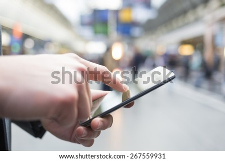 In hall station a man using his cell phone. Close-up hands - stock photo