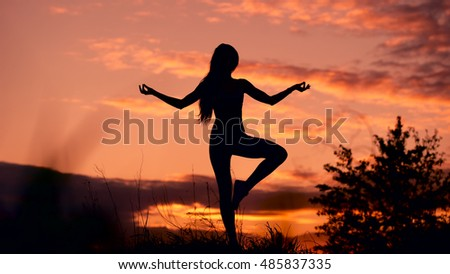 In harmony with oneself and the world. Silhouette of woman standing at yoga pose during an amazing sunset. Attractive, slim figure