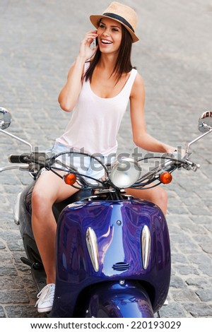 In her own style. Top view of beautiful young woman in funky hat sitting on scooter and smiling - stock photo