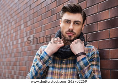 In his own style. Handsome young man leaning the wall and adjusting his scarf while leaning at the brick wall - stock photo