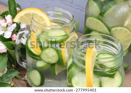 In hot summer day on the table decorated with apple tree blooms in backyard is served Naturally Flavored (Infused) Cucumber water with ice and lemon and lime slides