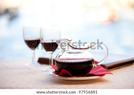 In Italy a Carafe a red wine - Chianti sits after being poured into glasses by the water under Rialto Bridge - stock photo