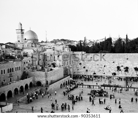 In Jerusalem, as sundown approaches on Shabbat, the Western Wall becomes crowded with people. The Dome of the Rock and a minaret are visible in the upper left. (Scanned from black and white film.) - stock photo