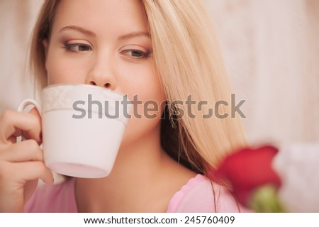 In love. Closeup image of young beauty drinking coffee in bed and looking at a red rose with selective focus - stock photo