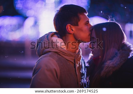 In love couple kissing in the snow at night city street. Filtered with grain and light flashing - stock photo