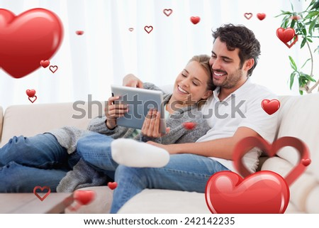 In love couple using a tablet computer against love heart pattern - stock photo