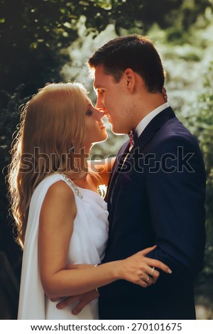in love cute bride and groom look at each other in the midst of green leaves light falls Montenegro