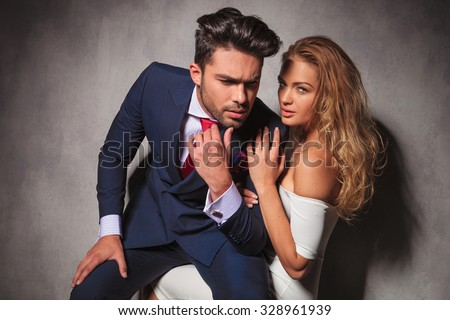 in love elegant couple, man sitting on his woman's lap and looks away from the camera thinking in studio