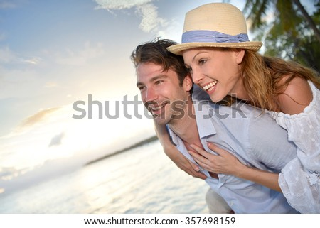 In love man giving piggyback ride to woman at the beach - stock photo