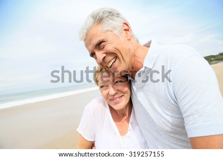 In love senior couple embracing at the beach - stock photo