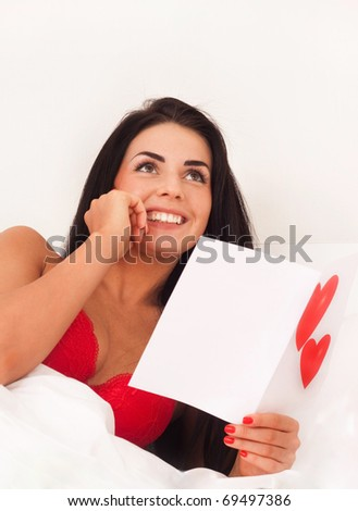 in love with a beautiful young girl lying in bed with gifts, cards, hearts. Feast day of St. Valentine - stock photo