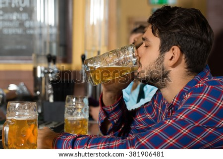 In love with beer. Horizontal closeup of a young handsome man drinking beer at the bar