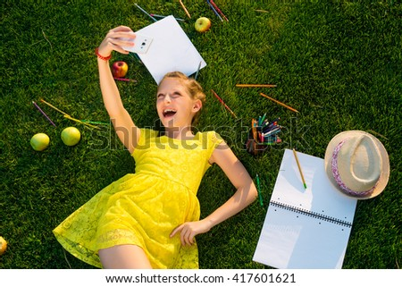 In love with camera and with strong and truthful emotions. Little caucasian princess knows how to enjoy her life and free time. Scattered stationery, apples and hat on green grass. - stock photo