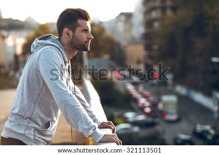 In love with his city. Side view of pensive young man in headphones looking away while standing on the bridge - stock photo