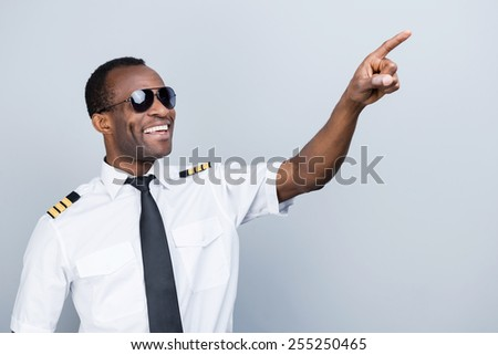In love with sky. Cheerful African pilot in uniform pointing away and smiling while standing against grey background - stock photo