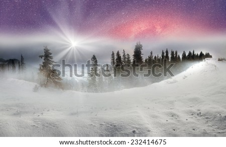 In March, the sudden cold and blizzard covered mountains, houses a silver snow fencing, morning and evening these days were especially beautiful when the sun breaks through heavy clouds with its rays  - stock photo