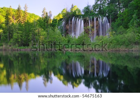 In midst of a natural forest a waterfall is reflected in a lake - stock photo