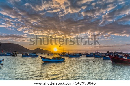 In Ninh Thuan, Vietnam - February 2nd, 2015: Sunrise over the pier with boat dock waiting to sail with yellow sky signaling a new day at sea beautiful start Ninh Thuan, Vietnam
