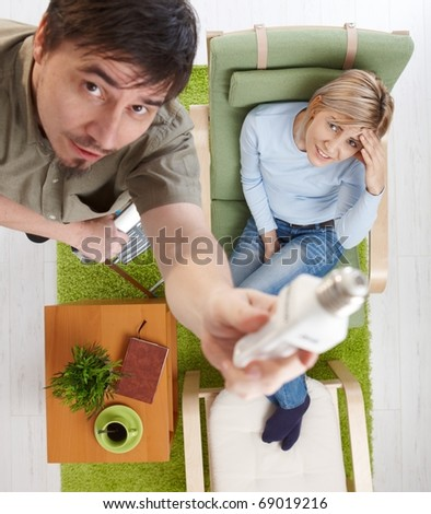 In overhead view man trying to change light bulb from ladder, woman looking up sitting in armchair, holding head, smiling.? - stock photo