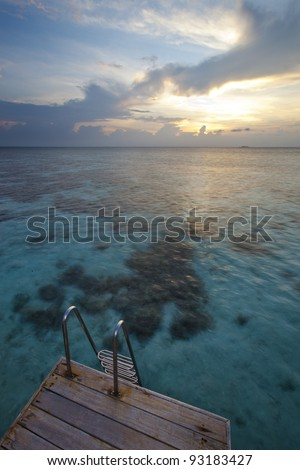 In paradise island, wood pontoon and scale front of a blue lagoon and sunset - stock photo