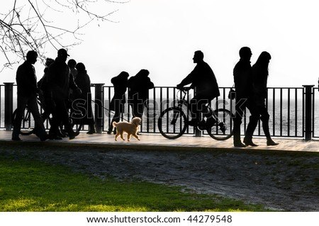 In park at the sea silhouettes of different people. - stock photo
