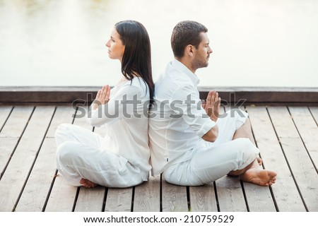 In peace with universe. Side view of beautiful young couple in white clothing meditating outdoors together while sitting back to back in lotus position - stock photo