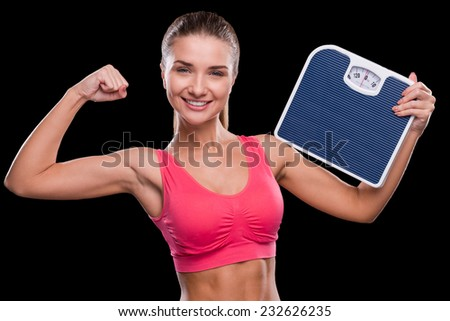 In perfect form. Sporty young woman holding weight scale and showing her bicep while standing against black background  - stock photo
