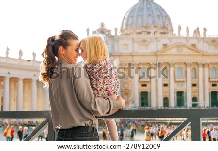 In profile, a mother and daughter give each other Eskimo kisses in Vatican City in Rome, Italy. In the background is St. Peter's Basilica and tourist crowds. - stock photo
