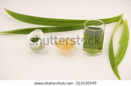 In row is freshly blended pandan leaf in paper tea bag, a clear bowl of cane rock sugar for sweet taste and the extracted green juice in glass.  Blur long pandan leaves at the background on white. - stock photo