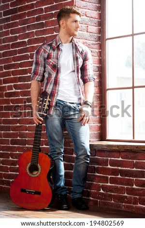 In search of inspiration. Full length of handsome young man holding acoustic guitar and looking through window  - stock photo