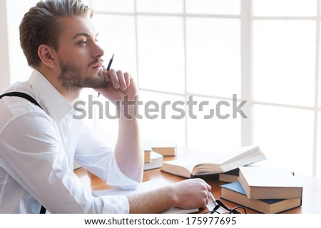 In search of inspiration. Thoughtful young man in shirt and suspenders holding hand on chin and looking away while sitting at the table with books laying on it - stock photo
