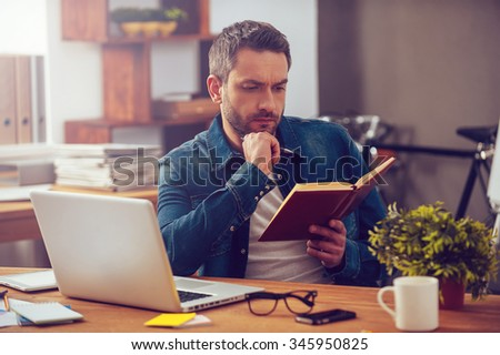 In search of inspiration. Thoughtful young man looking at his notebook while sitting at his working place in office - stock photo