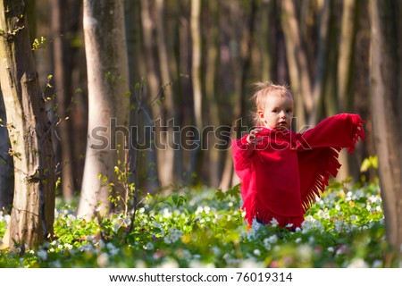 In spring forest funny little girl in the red trying to scare somebody - stock photo