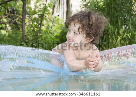 In summer, a bright sunny day in the garden in an inflatable pool bathing curly girl. - stock photo