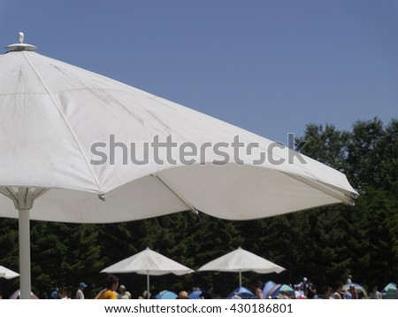 in summer day, people gather under parasols at park